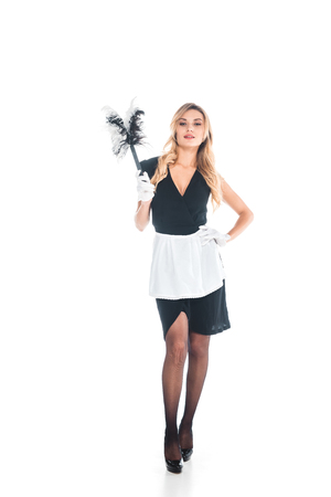 blonde attractive housemaid in black uniform, apron and gloves standing with broom on white background