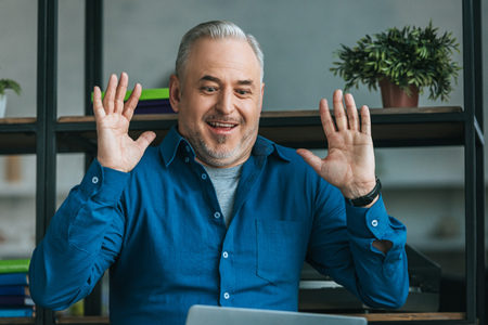 cheerful man putting hands up and smiling at home