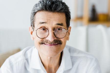 happy senior man in glasses smiling at home