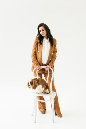 Stylish pregnant woman in suit looking at dog on chair on white background