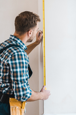 handyman standing and measuring wall with measuring tape Standard-Bild - 119072993