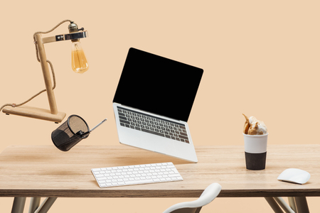 laptop with blank screen, lamp and stationery levitating in air above wooden desk with thermomug with coffee splash isolated on beige Standard-Bild - 119124583