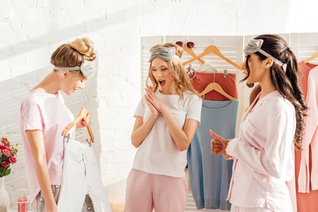 beautiful multicultural girls choosing clothes in wardrobe during pajama party in morning