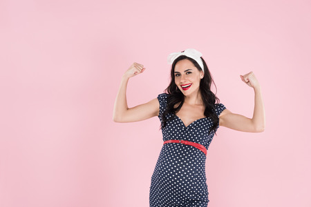 Happy pregnant woman in dress showing yes gesture isolated on pink