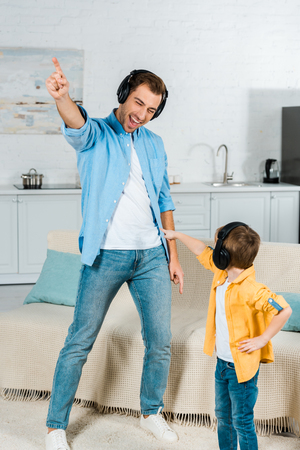 happy father with preschooler son in headphones listening music and pointing with fingers at home Stock Photo