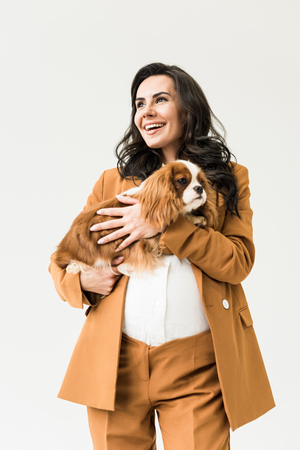 Excited pregnant woman in suit holding dog isolated on white
