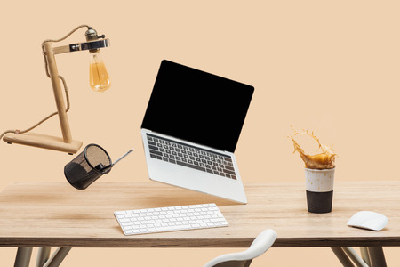 laptop with blank screen and lamp levitating in air above workplace with thermomug with coffee splash isolated on beige Standard-Bild - 118995812