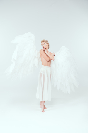 beautiful woman with angel wings covering breasts and posing with eyes closed isolated on white Stock Photo