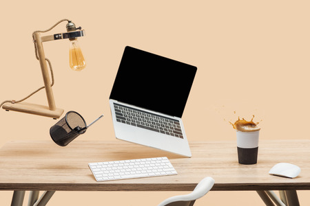 laptop with blank screen and lamp levitating in air above wooden desk with thermomug with coffee splash isolated on beige Standard-Bild - 118995830