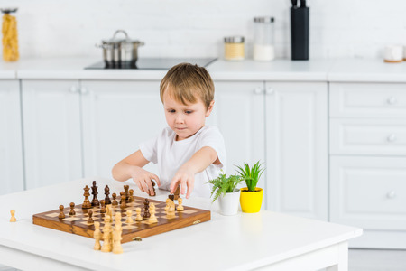 adorable preschooler boy sitting at table and playing chess at home
