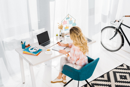 Blonde woman sitting at workplace and using laptop with blank screen Stock Photo