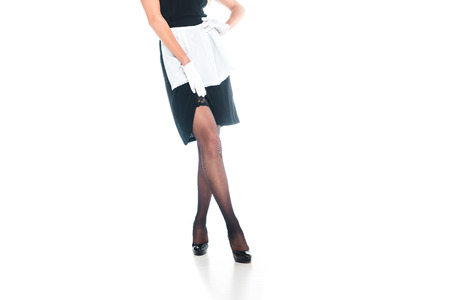 cropped view of housemaid in black uniform, gloves and apron with heel shoes on white background