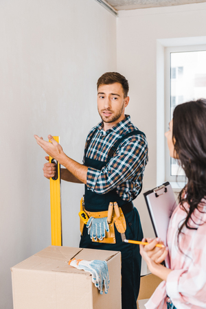selective focus of handyman gesturing and holding measuring level near woman with clipboard and looking at wall Standard-Bild - 118996459