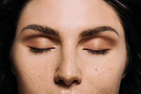 Vista cercana de la niña con los ojos cerrados y las pecas en la cara