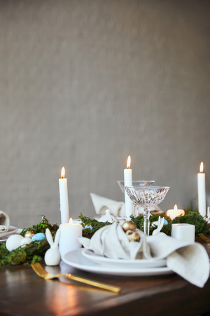 selective focus of quail eggs on napkin and plates near green moss, candles and crystal glasses on wooden table at home Stock Photo