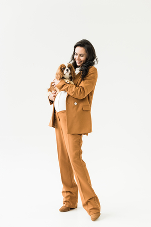 Full length view of pregnant woman in brown suit holding dog on white background