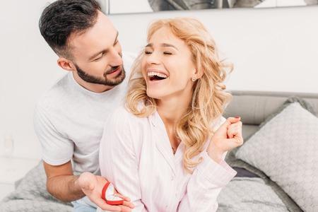 Brunette man proposing to laughing woman in bedroom Banco de Imagens