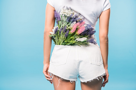 Cropped view of woman in shorts with flower bouquet in pocket on blue background