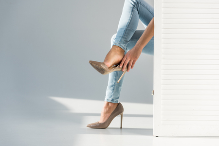 Partial view of woman putting on high-heeled shoes behind room divider on grey background