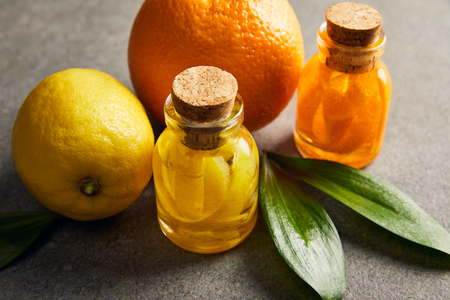 Essential oils with lemon and orange on dark surface