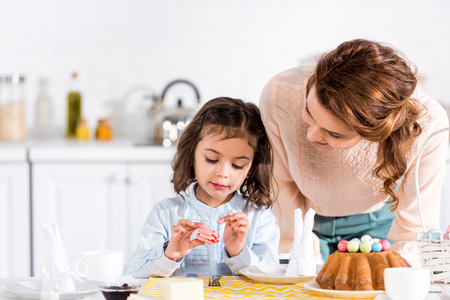 Brunette woman looking at daughter eating macaroon in kitchen Фото со стока