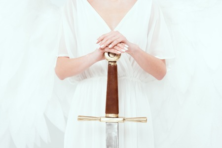 cropped view of woman with angel wings holding sword isolated on white Zdjęcie Seryjne