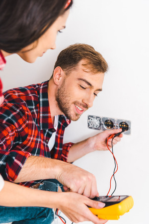 selective focus of man looking at digital multimeter while holding cables near girlfriend at home