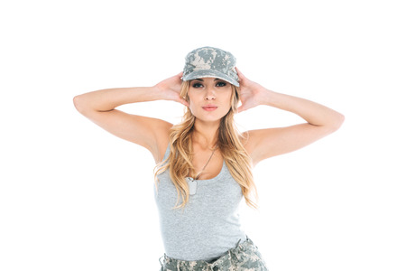 attractive militarywoman in grey t-shirt and camouflage cap isolated on white