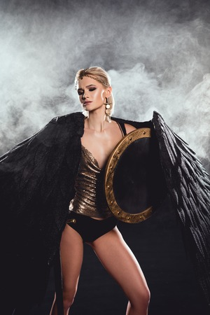 beautiful woman in warrior costume with black wings and shield posing on smoky background 版權商用圖片