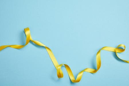 top view of yellow satin ribbon on blue background 版權商用圖片