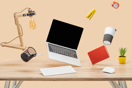 laptop with blank screen and stationery levitating in air above wooden desk isolated on beige 写真素材