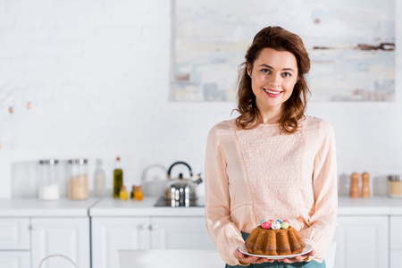 Smiling happy woman holding plate with easter bread in kitchen