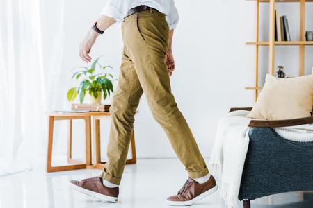 cropped view of senior man walking at modern home