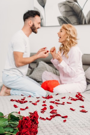 Man with beard sitting on bed with rose petals and making proposal to girlfriend