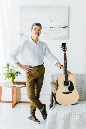 pensioner standing with crossed legs near acoustic guitar in living room