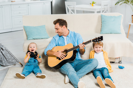 smiling father playing acoustic guitar to adorable happy preschooler and toddler sons at home