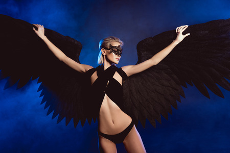 beautiful woman with lace mask and black angel wings posing on dark blue background