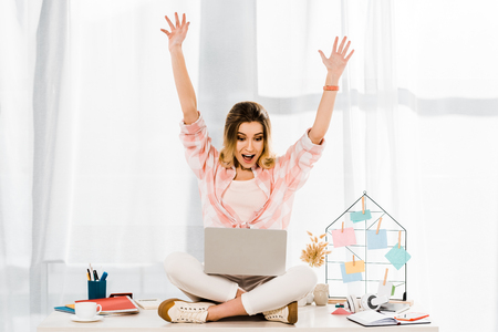 Amazed girl with laptop sitting on table and waving hands