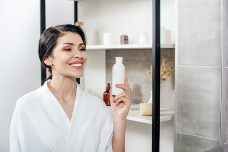woman in white bathrobe looking to mirror, holding bottle with lotion and smiling in bathroom Stok Fotoğraf