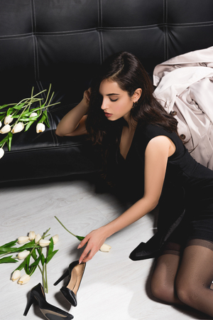 attractive brunette in black dress on floor with white tulips sitting near dark couch