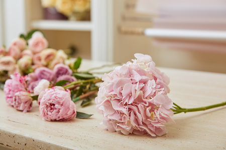 selective focus of pink roses and peonies on table