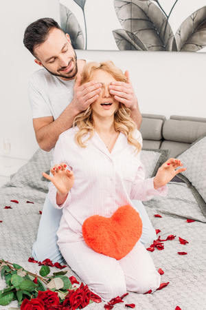 Man sitting on bed with roses and covering girlfriends eyes