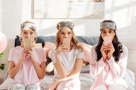 beautiful multicultural girls in sleeping masks sitting on bed and covering mouths with smartphones during pajama party