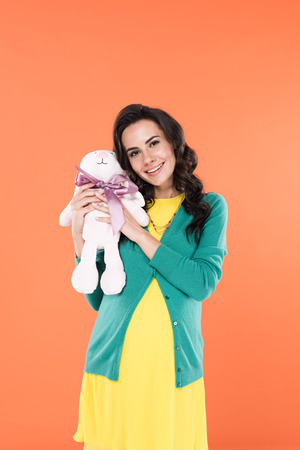 Blissful pregnant woman holding toy rabbit with smile isolated on orange Фото со стока