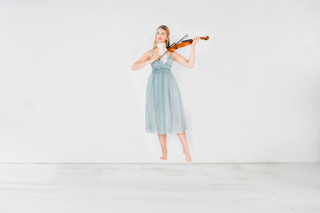floating girl in blue dress playing violin on white background with copy space