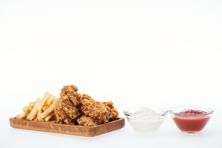 crispy chicken nuggets near french fries and glass bowls with ketchup and mayonnaise isolated on white