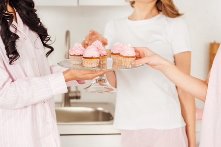 cropped view of girls taking cupcakes from glass stand during pajama party