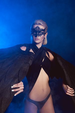 beautiful sexy woman in lace mask and black angel wings posing and looking away on dark blue background