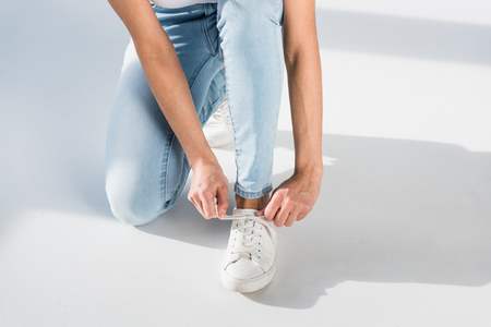 Partial view of woman in jeans tying shoelaces