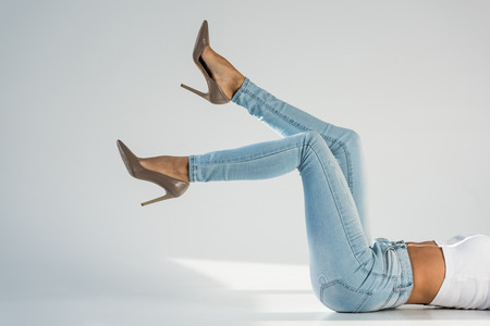 Partial view of young woman in jeans and high-heeled shoes on grey background
